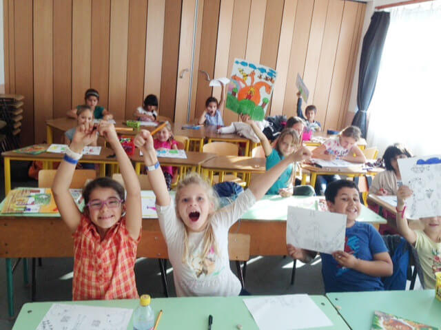 Children showing their drawings happily